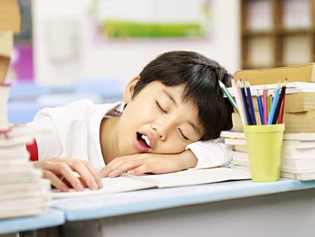 공부하는 동안 피곤하고 지쳐 아시아 초등학교 학생 잠들기 스톡 콘텐츠