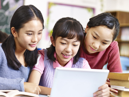 three asian elementary school girls friends looking at a tablet together during break in classroom. Imagens