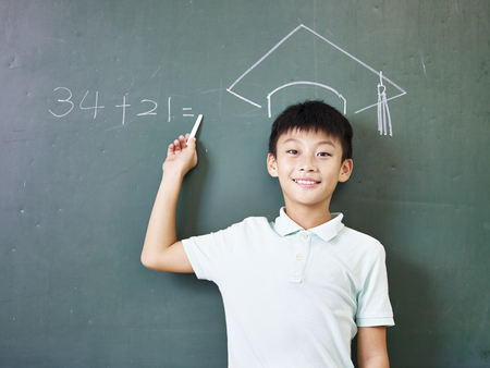 doctoral: asian elementary school boy standing under a doctoral hat drawn with chalk on blackboard.