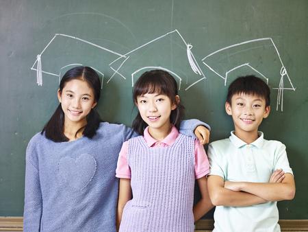 칠판 앞에 분필로 그려진 된 박사 모자 아래에 서있는 세 아시아 초등학교 어린이.