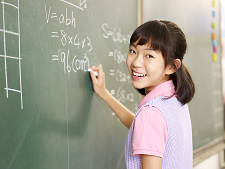 asian elementary schoolgirl looking at camera smiling while solving a math problem. 版權商用圖片
