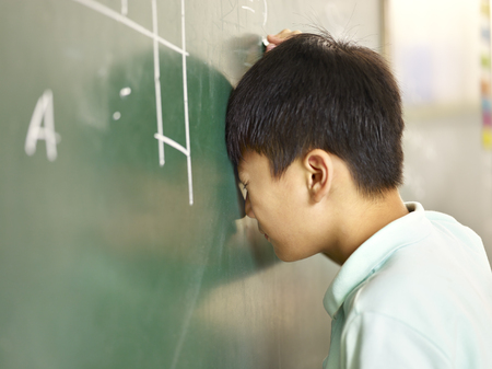 banging: painful asian elementary schoolboy banging his head on blackboard while solving geometry problem. Stock Photo