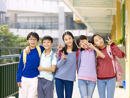 vigorously: group of happy smiling primary school student posing on corridor of classroom building.