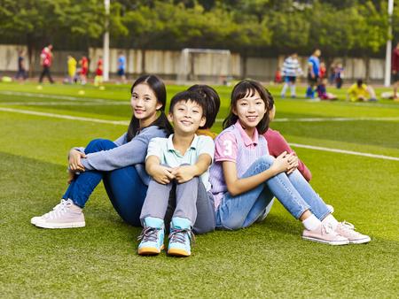 groep gelukkige lachende basisschool jongens en meisjes zitten op gras van speelplaats.