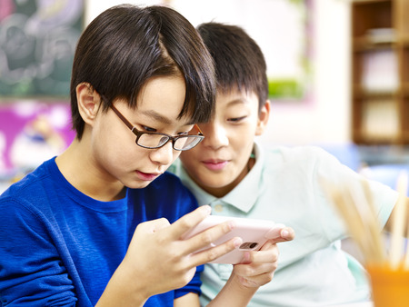 two asian primary school students playing online game using mobile phone. Banco de Imagens - 73724784