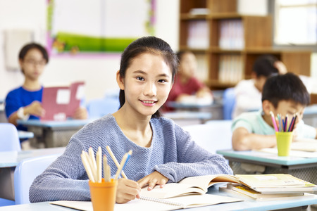 confident asian elementary school girl sitting in classroom looking at camera smiling. Reklamní fotografie