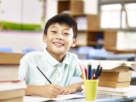 asian primary school student looking at camera smiling while studying in classroom.