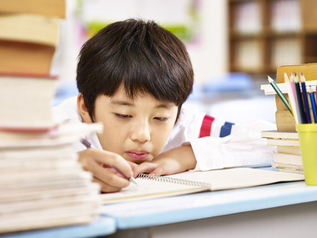tired and bored asian elementary school boy doing homework in classroom, head resting on desk.