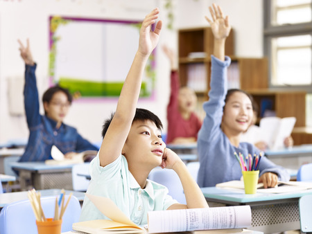 asian primary school pupils raising hands to answer questions in class.