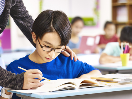 asian elementary school boy getting help from teacher in class.