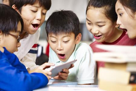Groupe d'élèves de l'école élémentaire asiatique se rassemblant autour du jeu en utilisant la tablette pendant la pause.