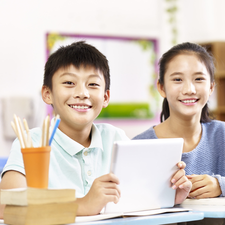 portrait of two happy asian primary school students looking at camera smiling. Imagens