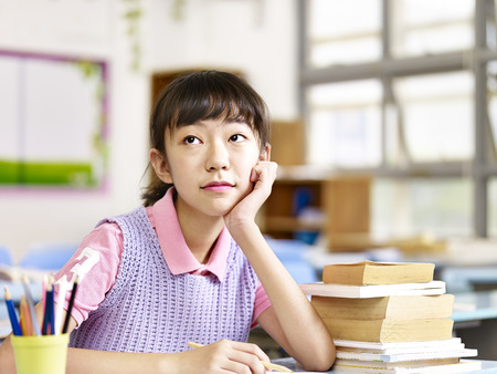 learning by doing: asian elementary schoolgirl sitting at desk looking up thinking in classroom.
