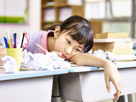 demotivated: asian elementary school girl frustrated after several failed attempts while writing an essay.