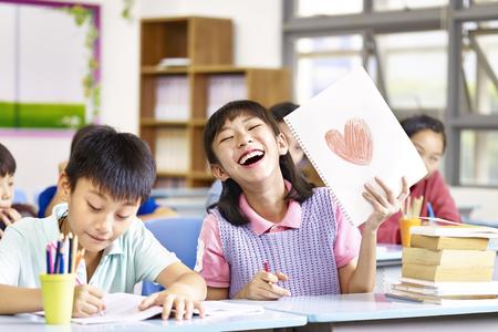 gelukkig en mooi Aziatisch elementair schoolmeisje dat een tekening en het lachen toont. Stockfoto