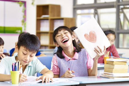 happy and lovely asian elementary school girl showing a drawing and laughing. Stock Photo