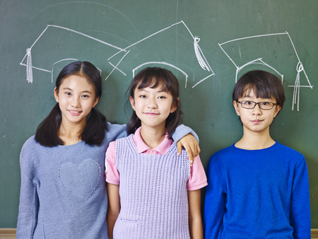three asian elementary school children standing in front of chalkboard underneath chalk-drawn doctoral caps. Zdjęcie Seryjne