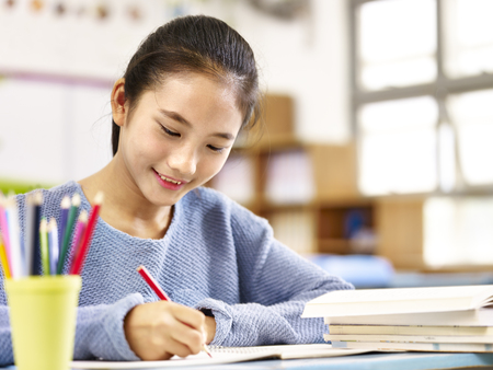 11 year-old asian schoolgirl doing homework, happy and smiling.