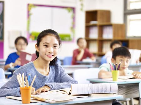 portret van Aziatische elementaire schoolmeisje zit in de klas met klasgenoten. Stockfoto