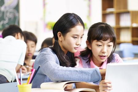그룹에서 작업하는 동안 태블릿 컴퓨터를 사용 하여 두 아시아 초등학교 여자.