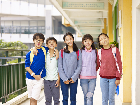 group of happy and smiling elementary schoolboys and schoolgirls standing in hallway of classroom building on campus. Stock Photo