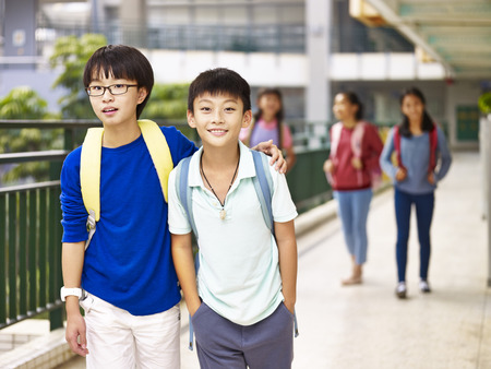 asian primary school students walking in hallway of classroom building.