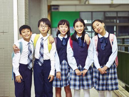 행복 하 고 웃는 초등학교 학생 유니폼에서의 그룹의 초상화.