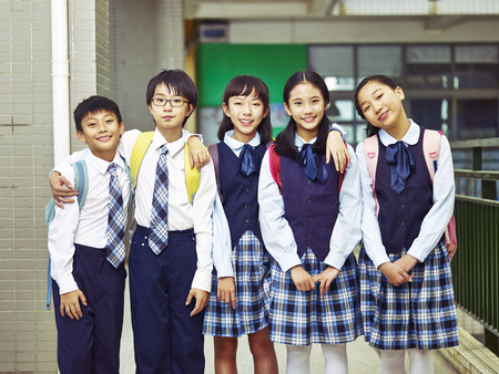 portrait of a group of happy and smiling elementary school students in uniform.