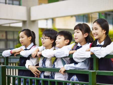 행복 하 고 웃는 초등 학생의 제복을 입은 그룹의 초상화. 스톡 콘텐츠