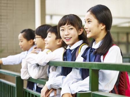 Aziatisch elementair schoolmeisje die camera bekijken die vol vertrouwen glimlachen. Stockfoto