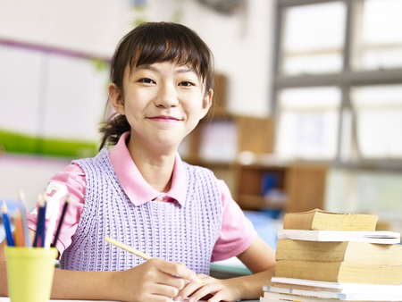 asian grade school student sitting at desk looking at camera smiling.