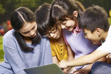 Aziatische elementaire schoolmeisjes en schooljongens met behulp van laptop buitenshuis samen. Stockfoto