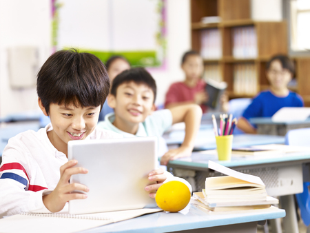asian elementary school child using tablet computer in classroom, happy and smiling.