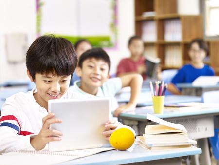 Aziatisch basisschool kind met behulp van tablet computer in de klas, blij en lachend. Stockfoto