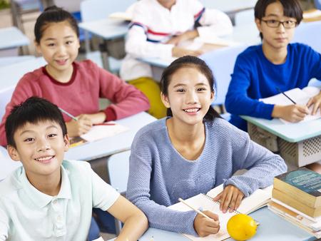azjatyckich uczniów szkół podstawowych siedzi w klasie, wysoki kąt widzenia. Zdjęcie Seryjne