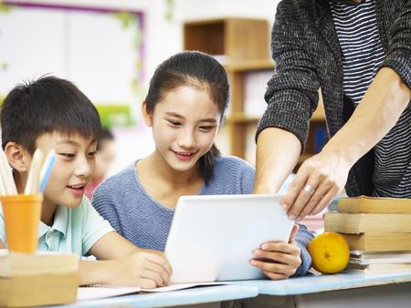 デジタル タブレットを使用して 2 つのアジアの小学校児童は教室で教師の家庭教師から助けます。 写真素材