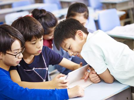 教室で一緒にデジタル タブレットを使用してアジアの小学生をグループ化します。 写真素材
