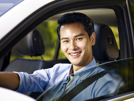 young asian adult man sitting in a car with safety belt on, looking at camera smiling. Stock Photo
