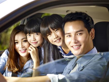 Gelukkige Aziatische familie met twee kinderen die in een auto rijden