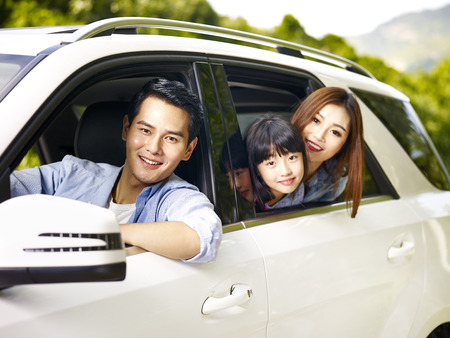 traveling: happy asian family traveling by car looking at camera smiling.