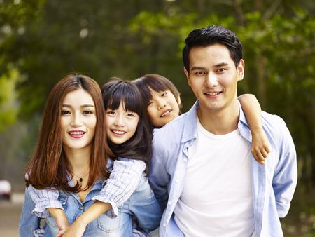나무가 우거진 된 공원에서 산책하는 두 아이의 행복 한 아시아 가족.