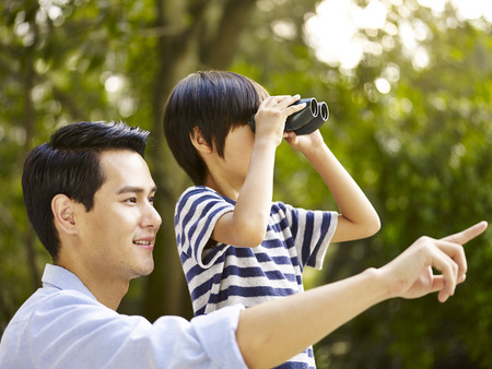 using binoculars: asian father and son using binoculars in park