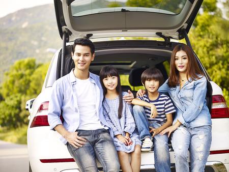 gelukkige Aziatische familie met twee kinderen die met de auto stellen waarin zij reizen. Stockfoto