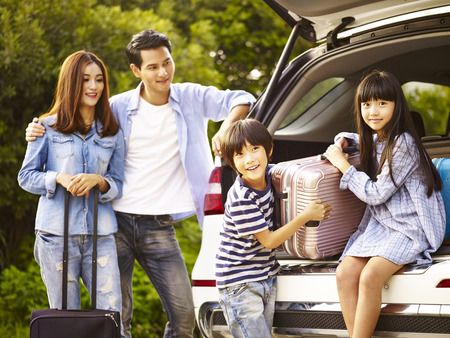 cute asian children helping unloading luggage from trunk while parents watching affectionately. Stock Photo