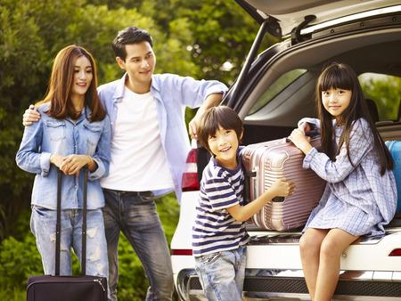 Niños asiáticos lindos ayudando a descargar el equipaje del maletero mientras que los padres ver con afecto. Foto de archivo