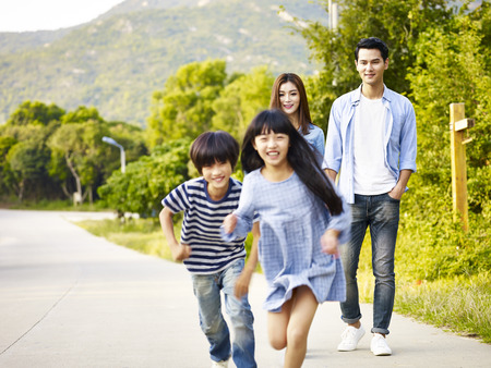 two asian children running in park while their parents watching affectionately. Stock Photo