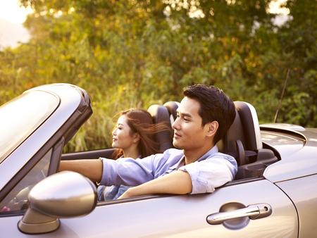 Jong Aziatisch paar rijden in een convertibele sportwagen bij zonsondergang.