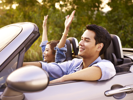 young asian couple riding in a convertible sport car at sunset.