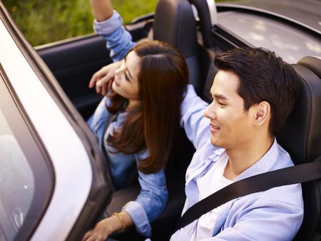 若いアジアのカップルは、日没、高い視野で転換のスポーツ車に乗って。 写真素材