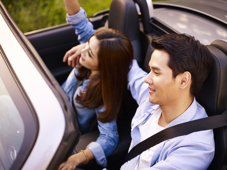 young asian couple riding in a convertible sport car at sunset, high angle view. Foto de archivo